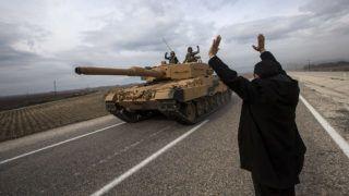 Reyhanli körzet, 2018. január 21.Tankkal elhaladó török tüzéreknek integet egy férfi a szíriai határ közelében levő Hatay déli tartomány Reyhanli körzetében 2018. január 21-én, miután a török haderő az előző napon szárazföldi hadműveletet indított Olajág fedőnéven a Népvédelmi Egységek (YPG) nevű kurd milícia ellenőrizte északnyugat-szíriai Afrín térségében. A beavatkozás eddig 153 célpontra mért csapást, köztük fegyverraktárakra és óvóhelyekre. (MTI/EPA/SedatSuna)