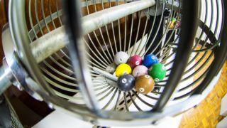 Equipamentos de loteria antigos com algumas bolas de sorteio dentro.