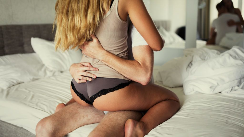 Passionate foreplay by couple wearing underwear in bedroom
