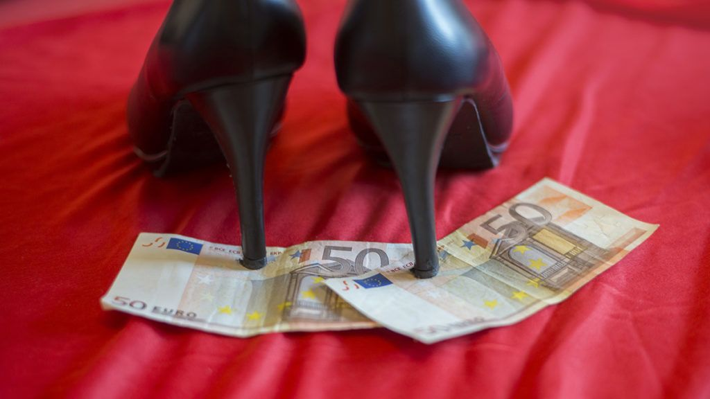 heels on 50 euro banknote on red bed