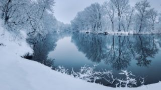 Winter forest on the river at sunset. Colorful landscape with snowy trees, beautiful frozen river with reflection in water. Seasonal. Winter trees, lake and blue sky. Frosty snowy river. Weather