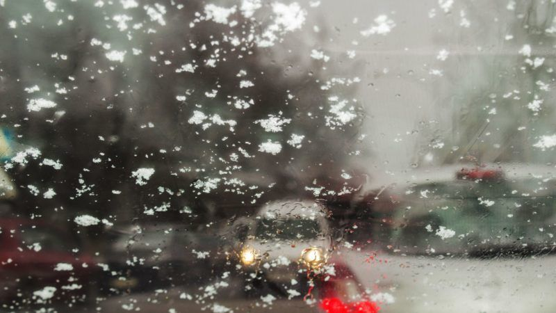 Outside the car the snow falls. Bad weather