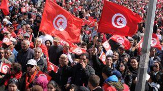 Tunisz, 2015. március 29.A tuniszi Bardo múzeum elleni terrortámadásra emlékező szolidaritási menet résztvevői nemzetiszínű zászlókkal Tuniszban 2015. március 29-én. Március 18-án az Iszlám Állam (IÁ) nevű terrorszervezet fegyveresei megtámadták a múzeumot és huszonhárom embert megöltek. (MTI/EPA)