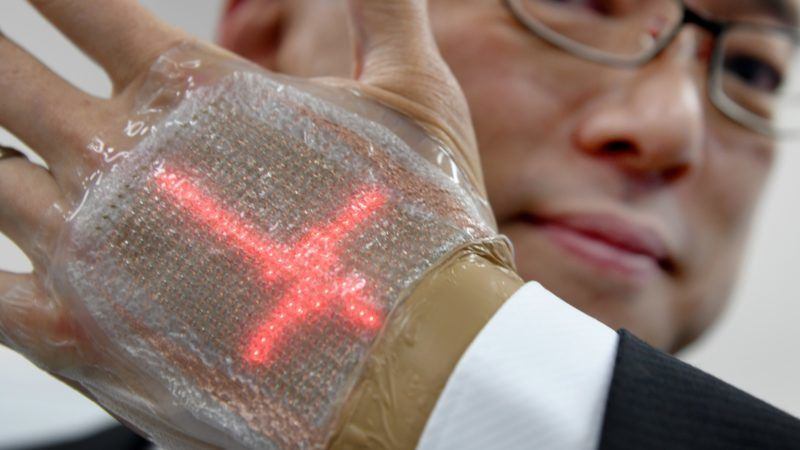 This photo taken on February 14, 2018 shows a man holding an ultra-thin elastic display equipped with a light emitting diode, newly developed by Professor Takao Someya of Tokyo University, in Tokyo. The band-aid-like device is just one millimetre thick and can monitor important health data as well as send and receive messages, including emojis. Someya, who developed the device, envisions it as a boon for medical professionals with bed-ridden or far-flung patients, as well as family living far from their relatives. / AFP PHOTO / TORU YAMANAKA