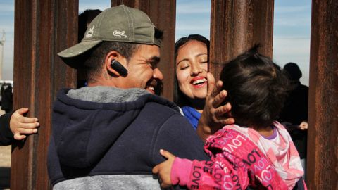 """Members of a family reunite through the border wall between Mexico and United States, during the """"Keep our dream alive"""" event, in Ciudad Juarez, Chihuahua state, Mexico on December 10, 2017.Families separated by the border are reunited for three minutes through the fence that separates Ciudad Juarez Park in Mexico and Sunland in New Mexico, United States, during an event called """"Keep our dream alive"""", organized by the Border Network for Human Rights on the International Human Rights Day.  / AFP PHOTO / Herika MARTINEZ"""