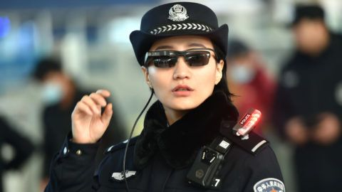 This photo taken on February 5, 2018 shows a police officer wearing a pair of smartglasses with a facial recognition system at Zhengzhou East Railway Station in Zhengzhou in China's central Henan province. Chinese police are sporting high-tech sunglasses that can spot suspects in a crowded train station, the newest use of facial recognition that has drawn concerns among human rights groups. / AFP PHOTO / - / China OUT
