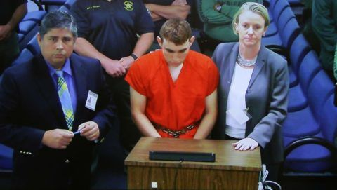 Hector Romero Asst. Public Defender(L) and Melisa McNeill, Public Defender (R) are seen on screen at the first appearance court for high school shooting suspect Nikolas Cruz(C) on February 15, 2018 at Broward County Court House in Fort Lauderdale, Florida. The heavily armed teenager who gunned down students and adults at a Florida high school was charged Thursday with 17 counts of premeditated murder, court documents showed. Nikolas Cruz, 19, killed fifteen people in a hail of gunfire at Marjory Stoneman Douglas High School in Parkland, Florida. Two others died of their wounds later in hospital, the sheriff's office said.  / AFP PHOTO / POOL / Susan STOCKER