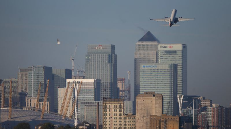A British Airway airplane climbs after taking off at London City Airport in London on October 27, 2017 with the towers and buildings of the Canary Wharf financial district in background. British Airways parent group IAG forecast on October 27 a 20-percent jump in operating profit this year thanks to rising demand and falling costs. Operating profit before exceptional items, and at current fuel prices and exchange rates, was forecast to hit 3.0 billion euros ($2.7 billion) in 2017, IAG said in an statement. That was up from 2.5 billion euros in 2016.  / AFP PHOTO / Daniel LEAL-OLIVAS