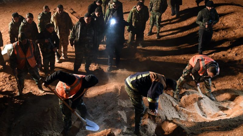 EDITORS NOTE: Graphic content / Syrian forces excavate a site, said to be a mass grave by state news agency SANA, west of Raqa province, on December 29, 2017. Two mass graves containing dozens of bodies of civilians and Syrian troops killed by Islamic State jihadists have been found in the west of Raqa province, state news agency SANA reported.  / AFP PHOTO / George OURFALIAN