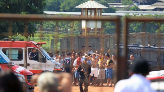 """This photo released by Brazilian newspaper O Popular shows families of prisoners watching guards move inmates at the """"Coronel Odenir Guimaraes"""" State Prison in Aparecida de Goiania, Goias, Brazil, on January 1, 2018.  Nine prisoners were killed and 14 injured in a riot on New Year's Day triggered by a fight between rival groups. According to the Goias security secretariat, 233 inmates escaped. Although many returned on their own, around 100 are still missing. / AFP PHOTO / O Popular / Claudio REIS"""