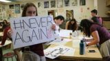 """A student holds a sign reading """"Never Again"""" as students from North Broward Preparatory School in Coconut Creek, Florida prepare towalk out of class to protest gun violence on February 20, 2018. There have been renewed calls for stricter gun control in the United States following the shooting deaths last week of 14 students and three adults at the Marjory Stoneman Douglas High School on February 14. The White House has said following the Florida school shooting that President Donald Trump supports efforts to improve the federal background check system for gun buyers."""