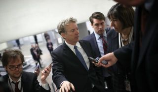 WASHINGTON, DC - FEBRUARY 08: Sen. Rand Paul (R-KY) speaks with reporters on his way to a vote on the floor of the U.S. Senate at the U.S. Capitol February 8, 2018 in Washington, DC. Paul is blocking the U.S. Senate from voting on a spending package reached yesterday to avoid a government shutdown. Paul is demanding that the U.S. Senate vote on an amendment that would cap spending.   Win McNamee/Getty Images/AFP