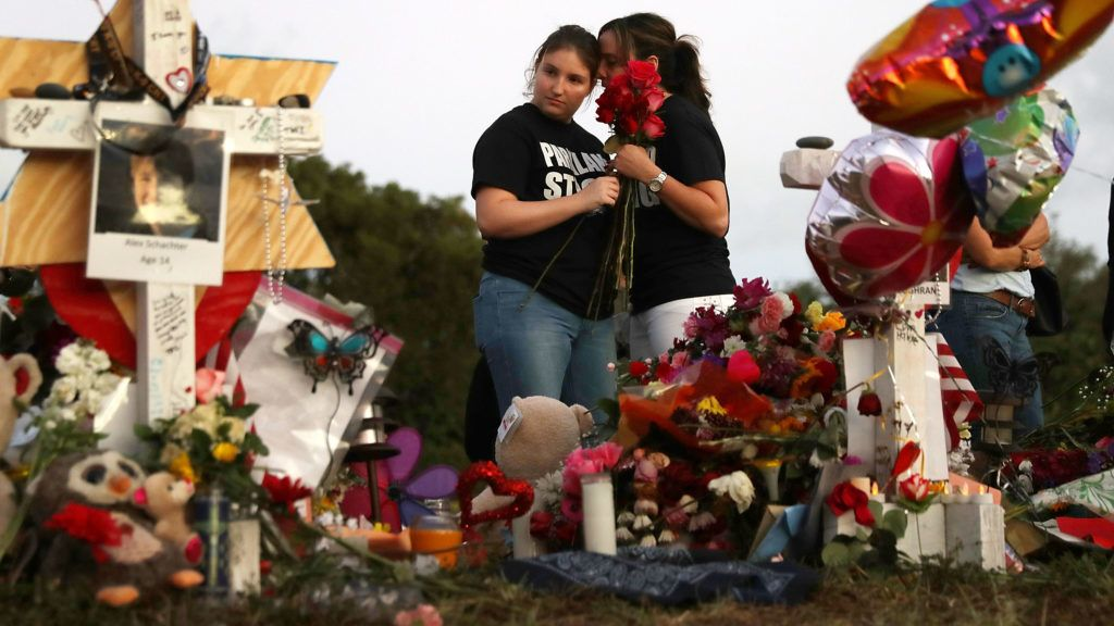PARKLAND, FL - FEBRUARY 21: Alexa Mesch (L) and Heather Mesch place flowers in a makeshift memorial setup in front of Marjory Stoneman Douglas High School in memory of the 17 people that were killed on February 14, on February 21, 2018 in Parkland, Florida. Police arrested 19-year-old former student Nikolas Cruz for killing 17 people at the high school.   Joe Raedle/Getty Images,/AFP