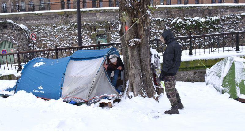 PARIS, FRANCE - FEBRUARY 10: Migrants exposed freezing temperature as snow, shelter tents near the Canal Saint-Martin in Paris, France on February 10, 2018. Migrants try to live in hard conditions during winter season.  Nedim / Anadolu Agency