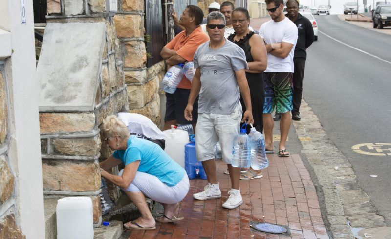 People collect drinking water from pipes fed by an underground spring, in St. James, about 25km from the city centre, on January 19, 2018, in Cape Town.  Cape Town will next month slash its individual daily water consumption limit by 40 percent to 50 litres, the mayor said on January 18, as the city battles its worst drought in a century. / AFP PHOTO / RODGER BOSCH