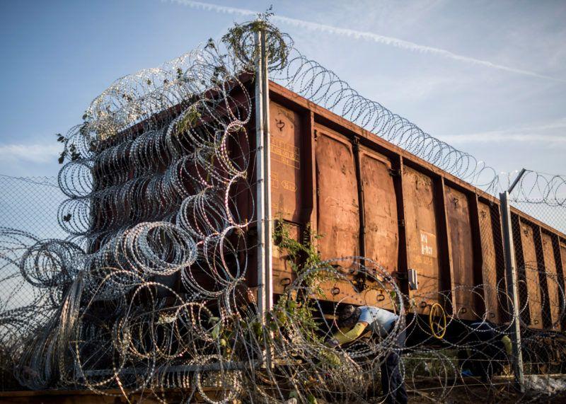 Horgos, 2015. szeptember 15.Szögesdrótot szerelnek fel a határzárként használt vasúti vagonra a magyar-szerb határnál, Röszke térségében 2015. szeptember 15-én. Ezen a napon hatályba léptek a migrációs helyzet miatti új szabályozások.MTI Fotó: Mohai Balázs