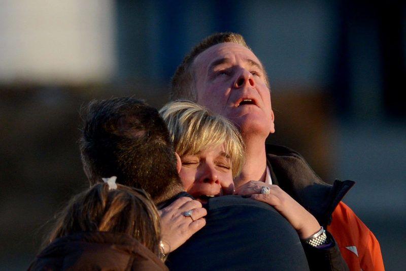 Newton, 2012. december 14.Hozzátartozók vigasztalják egymást 2012. december 14-én, azt követően, hogy egy Adam Lanza nevű 20 éves férfi agyonlőtt 26 embert, köztük 20 kisgyereket a Connecticut állambeli Newton városban lévő Sandy Hook általános iskolában. A férfi a szüleit is megölte. Obama amerikai elnök négynapos nemzeti gyászt rendelt el. (MTI/EPA/Justin Lane)