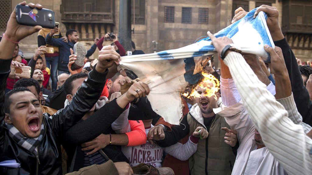 Kairó, 2017. december 8.Izraeli zászlót égetnek egyiptomi muszlimok a kairói Azhar mecsetben 2017. december 8-án. Két nappal korábban Trump bejelentette, hogy az Egyesült Államok Tel-Aviv helyett Jeruzsálemet tekinti Izrael fővárosának. (MTI/EPA/Mohamed Hoszam)