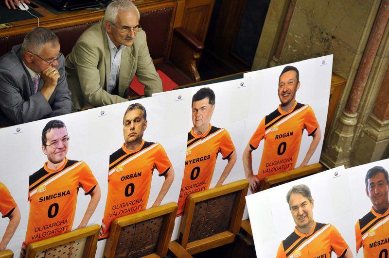 Budapest, 2012. június 14.A Demokratikus Koalíció (DK) független képviselői transzparenseket állítottak fel az ülésteremben, az Országgyűlés plenáris ülésének kezdete előtt. A táblákon szereplők a hátsó sorban, balról jobbra: Simicska Lajos korábbi APEH-elnök, Orbán Viktor miniszterelnök, Nyerges Zsolt, a Közgép Zrt. elnöke, Rogán Antal, a Fidesz frakcióvezetője, a főváros V. kerületének polgármestere. Az első sorban balról jobbra: Törcskei István, az Államadósság Kezelő Központ (ÁKK) Zrt. vezérigazgatója és Mészáros Lőrinc, a Puskás Ferenc Labdarúgó Akadémia kuratóriumának elnöke, Felcsút polgármestere.MTI Fotó: Kovács Attila