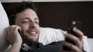 Man reclining in bed talking on phone and looking at second smart phone