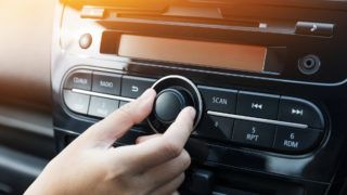 Women turning button on car radio for listening to music