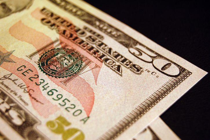 A fifty dollar bill on a black background