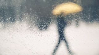 Abstract blurred snowy and rainy person walk with yellow umbrella. View from rainy car glass window. Conceptual bad weather background.