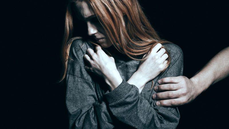 Fearful rape victim, man holding her arm, black background