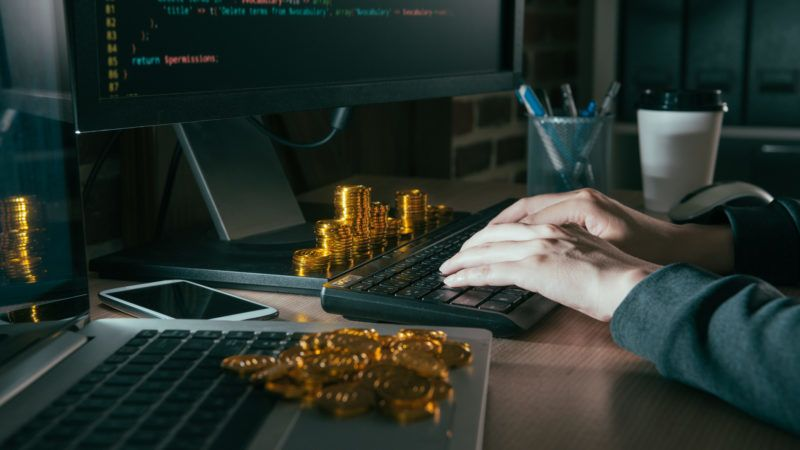 closeup photo of hacker using computer internet virus and typing data steal information in order to request ransom bitcoin gold.