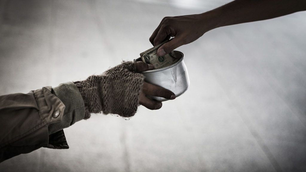 A hand give money to homeless people