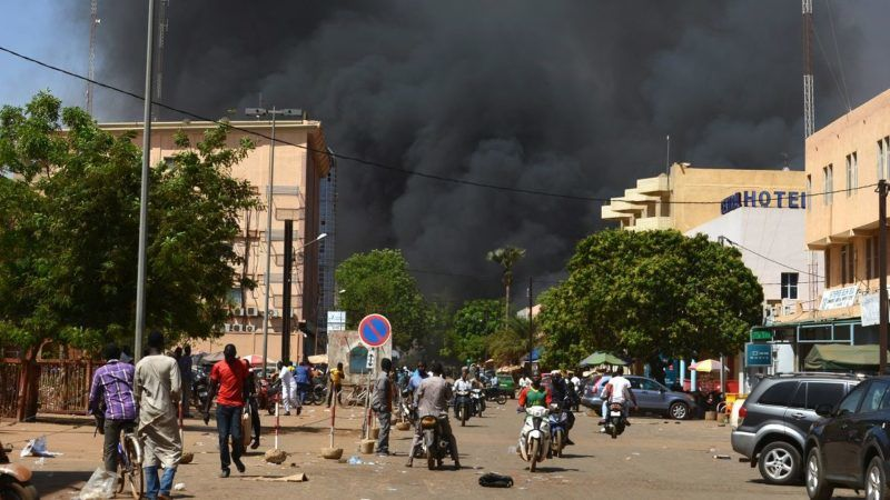 People watch as black smoke rises as the capital of Burkina Faso came under multiple attacks on March 2, 2018, targeting the French embassy, the French cultural centre and the country's military headquarters. Witnesses said five armed men got out of a car and opened fire on passersby before heading towards the embassy, in the centre of the city. Other witnesses said there was an explosion near the headquarters of the Burkinabe armed forces and the French cultural centre, which are located about a kilometre (half a mile) from the site of the first attack.  / AFP PHOTO / Ahmed OUOBA