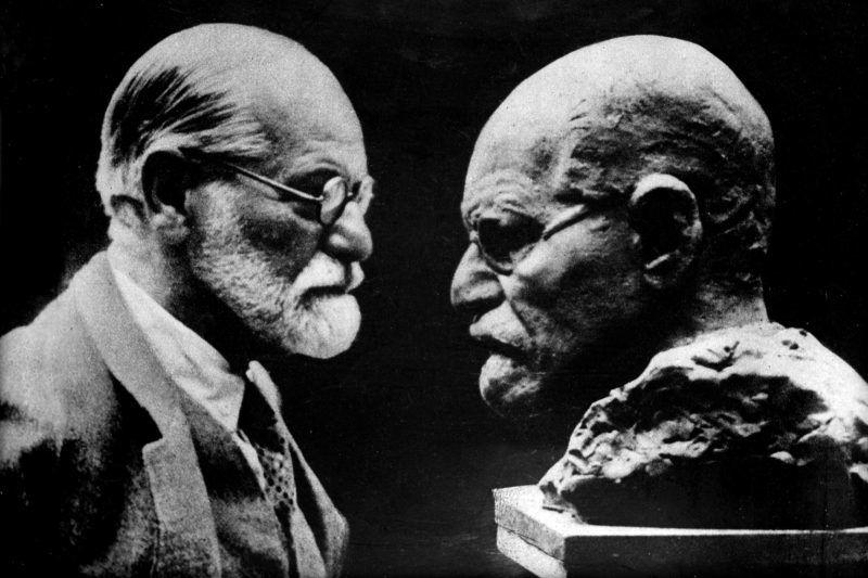 Sigmund Freud (1856-1939), médecin autrichien, fondateur de la psychanalyse, regardant son buste exécuté par Némond.     HRL-602996