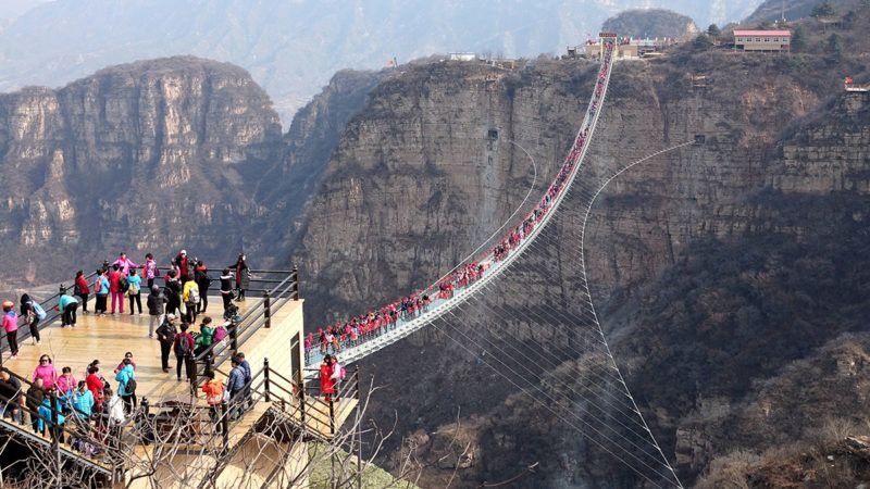 Tourists throng to walk on the world's longest glass bridge in the Hongyagu Scenic Area in Pingshan county, Shijiazhuang city, north China's Hebei province, 20 March 2018.The world's longest glass bridge attracted tourists in Shijiazhuang, Hebei province on Tuesday (20 March 2018). The bridge, which stretches 488 meters, is 2 meters wide and hangs 218 meters (about 66 stories) above the valley floor between two steep cliffs in the Hongyagu Scenic Area in Pingshan county. It is paved with 1,077 panes of transparent glass, each 4 centimeters thick, and weighs a total of 70 metric tons. The sky bridge is designed to swing a little while visitors walk to its centre, creating a thrill for visitors, according to Hebei Bailu Group, the local tourism company that built the bridge. While walking on the bridge, tourists can enjoy the surrounding Hongyagu scenery, which boasts a unique geographic landscape with mountain views, natural waterfalls, ancient towns and temples. The bridge was designed to support up to 2,000 people, though it's expected that only 500 will be on it at one time, said Liu Qiqi, director in charge of construction.