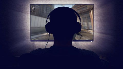 Gamer in headphones sits in front of a blank monitor in dark room