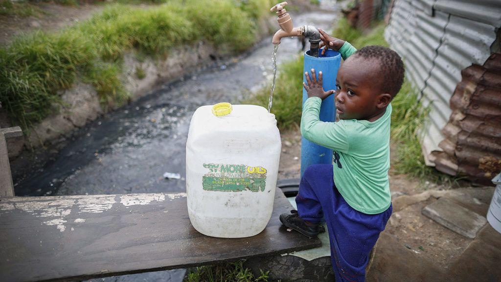 Fokváros, 2018. január 30.Dél-afrikai kisfiú egy ivóvízzel telő műanyag kannánál Fokvárosban 2018. január 30-án. A több éve tartó aszály és az éghajlatváltozás miatt súlyos vízhiánnyal küzdő Fokvárosnak körülbelül három hónapra elegendőek a víztartalékai. Ha nem sikerül széles körben rávenni a lakosságot a vízzel való takarékoskodásra, akkor április 22-én elzárják vízcsapokat, mivel nem marad víz a tározókban. Amennyiben ez megtörténik, Fokváros lesz a világon az első nagyváros, ami kifogy az ivóvízből. (MTI/EPA/Nic Bothma)