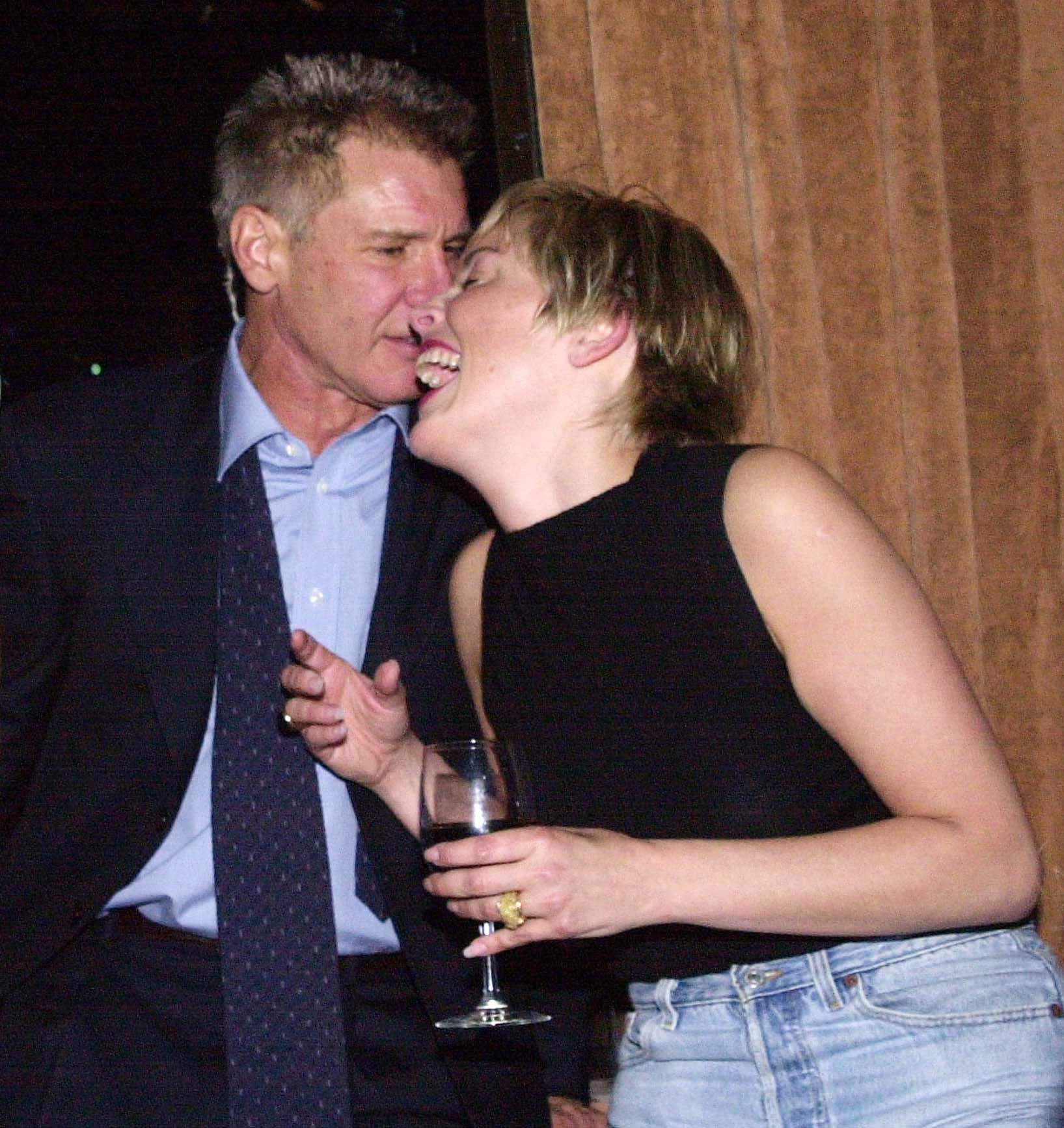 """Actor Harrison Ford and actress Sharon Stone share a light moment at GQ Magazine's party 16 February 2000 to unveil its March 2000 issue, """"Leading Men of Hollywood,"""" featuring Ford on the cover.    (ELECTRONIC IMAGE) / AFP PHOTO / JIM RUYMEN"""