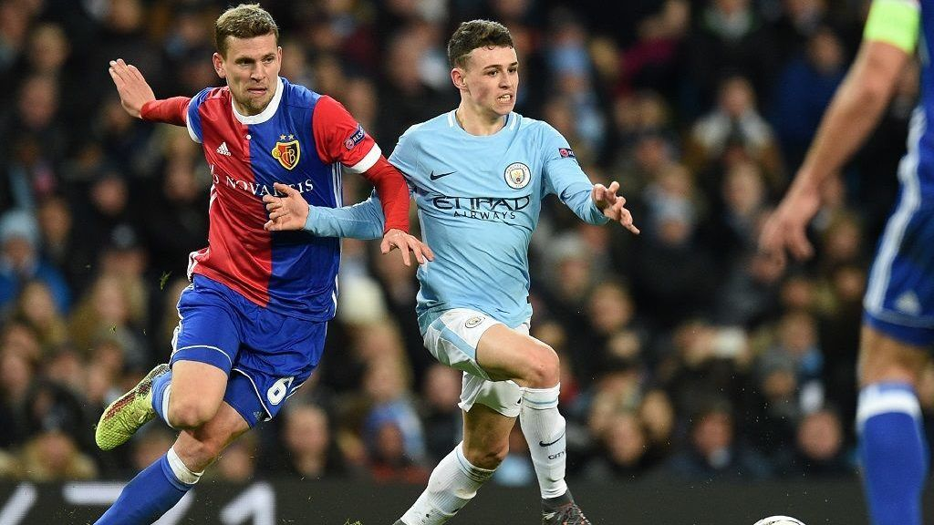 Basel's Swiss midfielder Fabian Frei (L) vies with Manchester City's English midfielder Phil Foden during the UEFA Champions League round of sixteen second leg football match between Manchester City and Basel at the Etihad Stadium in Manchester, north west England, on March 7, 2018. / AFP PHOTO / Oli SCARFF