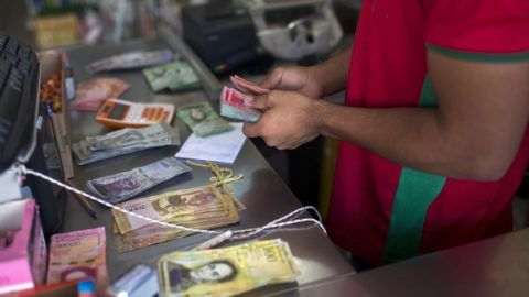 A Brazilian shopkeeper counts Venezuelan money received from Venezuelans crossing the border to buy food at Pacaraima, Roraima, Brazil, on February 27, 2018.   According to local authorities, around one thousand refugees are crossing the Brazilian border each day from Venezuela. With the constant influx of Venezuelan immigrants, most are living in shelters and the streets of Boa Vista and Pacaraima cities, looking for work, medical care and food. Most are legalizing their status to stay and live in Brazil.  / AFP PHOTO / Mauro Pimentel / TO GO WITH AFP STORY by Paula RAMÓN