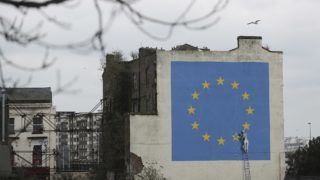 A mural by British artist Banksy, depicting a workman chipping away at one of the stars on a European Union (EU) themed flag, is pictured in Dover, south east England on March 19, 2018. Britain and the European Union on March 19, 2018 reached a landmark deal on a transition phase that will last for nearly two years after the historic Brexit divorce next year, EU negotiator Michel Barnier said. / AFP PHOTO / DANIEL LEAL-OLIVAS / RESTRICTED TO EDITORIAL USE - MANDATORY MENTION OF THE ARTIST UPON PUBLICATION - TO ILLUSTRATE THE EVENT AS SPECIFIED IN THE CAPTION
