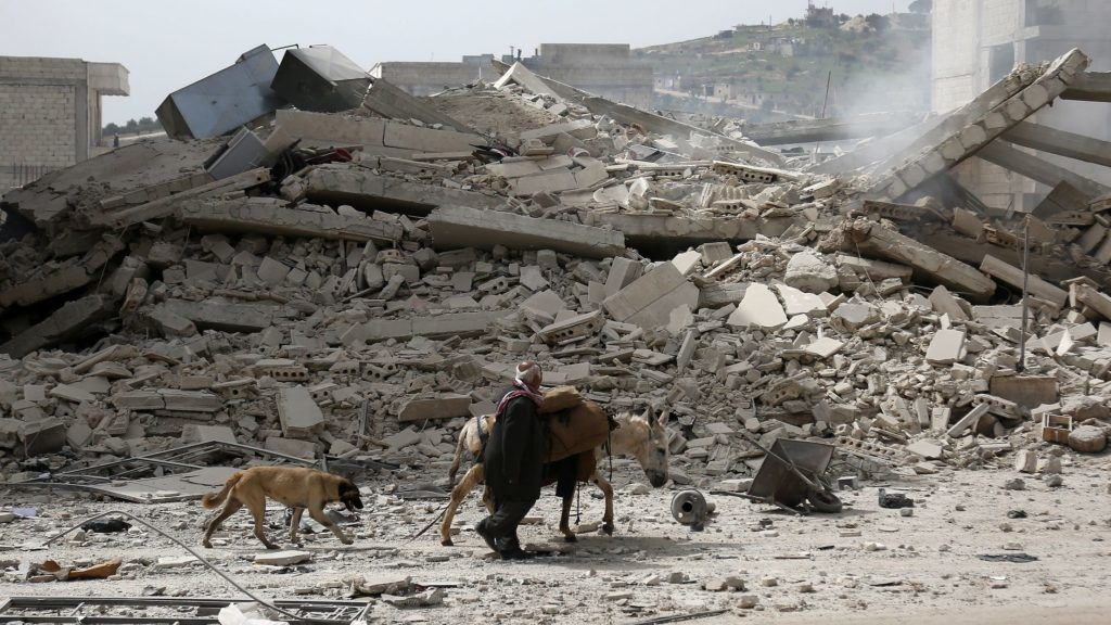 A picture taken on March 22, 2018 shows a man walking with a loaded donkey and followed by a dog past the rubble of a destroyed building in the northwestern Syrian city of Afrin. / AFP PHOTO / Nazeer al-Khatib