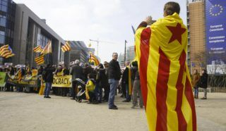 A man wrapped in a Catalan flag takes pictures of people taking part in a protest march of Catalans supporters in front of the European Commission's headquarters, during a rally in Brussels, on March 25, 2018. German police on March 25, 2018 arrested Catalonia's former president Carles Puigdemont as he crossed the border with Denmark by car after Spain's Supreme Court vowed to prosecute 13 key separatists over their breakaway bid. / AFP PHOTO / BELGA / NICOLAS MAETERLINCK / Belgium OUT