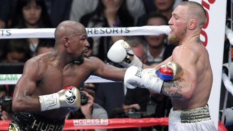 Mixed martial arts star Conor McGregor (R) competes with boxer Floyd Mayweather Jr. during their fight at the T-Mobile Arena in Las Vegas, Nevada on August 26, 2017.  Floyd Mayweather outclassed Conor McGregor with a 10th-round stoppage on August 26 to win their money-spinning superfight and clinch his 50th straight victory. / AFP PHOTO / John Gurzinski