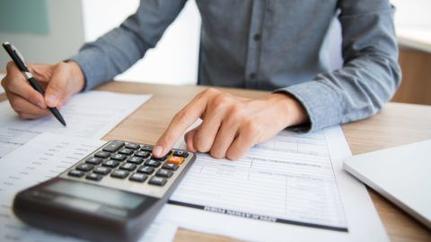 Unrecognizable accountant examining financial report. Male hands using calculator at desk. Businessman preparing annual report in office. Paperwork concept