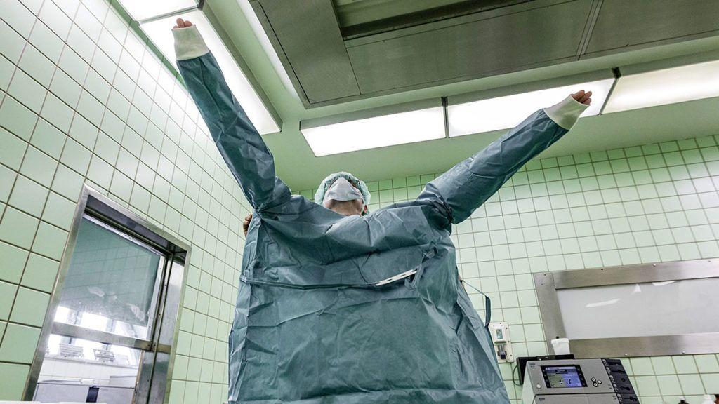 Budapest, 2015. június 30.Egy asszisztens steril műtőkabátot vesz magára egy műtét előtt a Semmelweis Egyetem Transzplantációs és Sebészeti Klinika műtőjében 2015. június 30-án. Minden év július 1-jén, Semmelweis Ignác születésnapján ünneplik a magyar egészségügy napját, a Semmelweis-napot.MTI Fotó: Szigetváry Zsolt