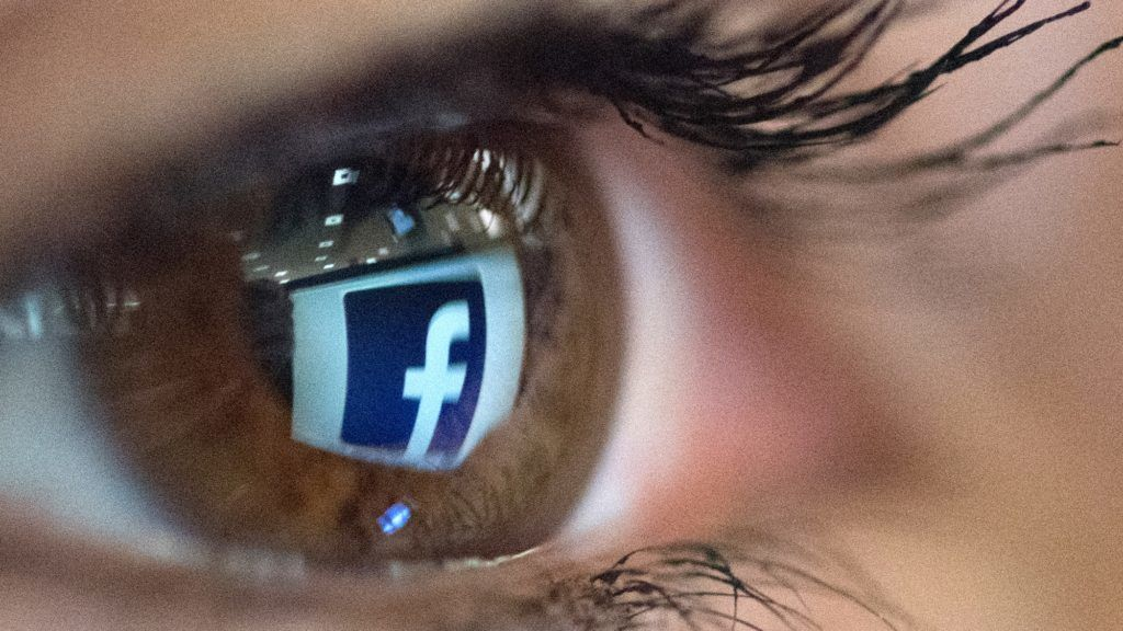 An illustration picture taken on March 22, 2018 in Paris shows a close-up of the Facebook logo in the eye of an AFP staff member posing while she looks at a flipped logo of Facebook.  / AFP PHOTO / Christophe SIMON