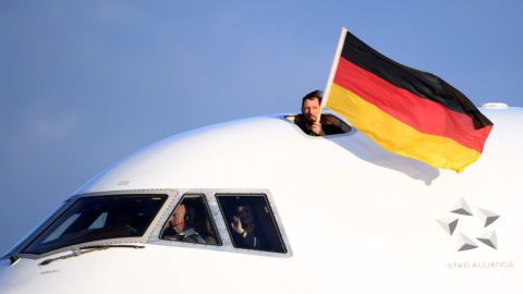 A man holds a German flag from a hatch in the cockpit after a Lufthansa LH713 machine transporting more than 150 athletes, coaches and officials on board arrives at the airport in Frankfurt am Main, Germany, following the 2018 PyeongChang Olympic Games, on February 26, 2018. / AFP PHOTO / dpa / Arne Dedert / Germany OUT