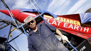 """Amboy, 2017. november 28. """"Mad"""" Mike Hughes amerikai sofõr, autodidakta rakétakutató a másodlagos felhasználású anyagokból saját maga által megépített gõzhajtású rakétájával a kaliforniai Amboy közelében 2017. november 27-én. A 61 éves Hughes azt tervezte, hogy november 25-én kilövi magát a rakétájával az elnéptelenedett kaliforniai város, Amboy közelébõl, hogy az utazása alatt készíteni tervezett fényképekkel  bebizonyítsa, hogy a Föld lapos és lemez formájú. Ám a megfelelõ engedélyek hiányában, valamint a rakétakilövõként szolgáló berendezéssel, azaz a lakókocsijával adódott problémák miatt eddig erre nem kerülhetett sor. A rakéta feliratának jelentése: Kutatás – Lapos Föld. (MTI/EPA/Paul Buck)"""