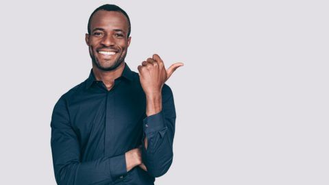 Handsome young African man pointing away and smiling to you while standing against grey background