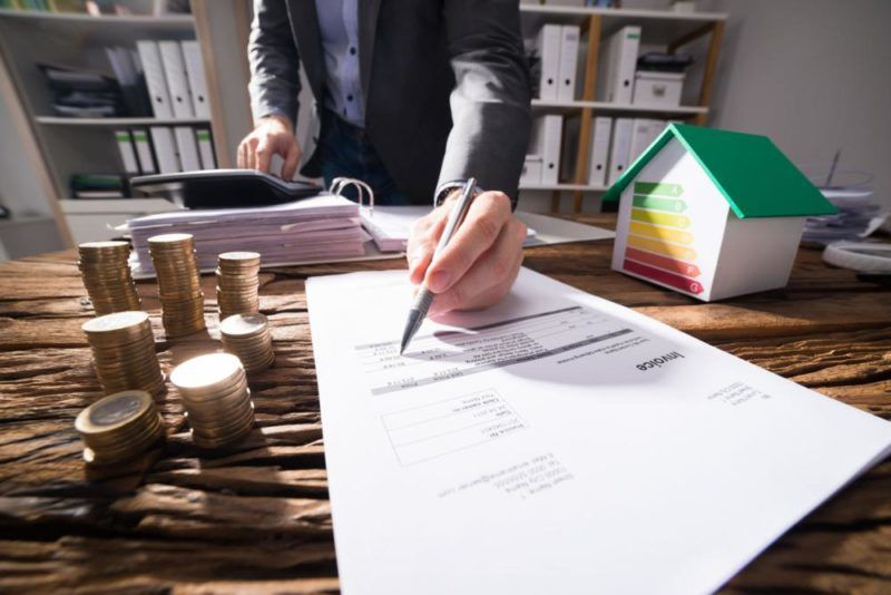 94459021 - businessperson calculating bill with coins and house model showing energy efficiency rate on desk