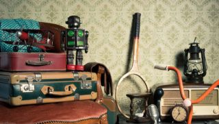Assorted vintage items in the attic with retro wallpaper background.
